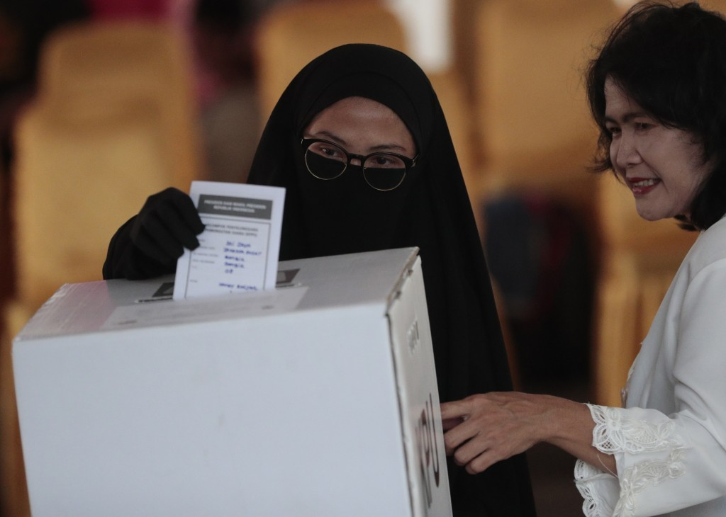 A Muslim woman casts her ballot during the election at a polling station in Jakarta, Indonesia, Wednesday, April 17, 2019. Voting is underway in Indon...
