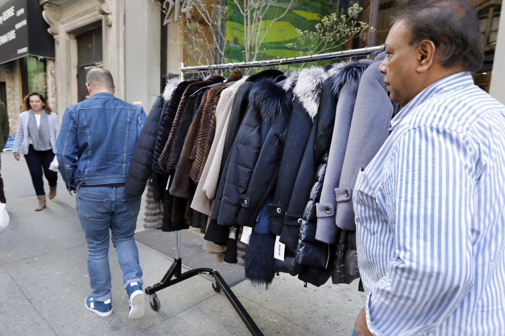 In this April 10, 2019, photo, two men push a rack of coats in the Fur District in New York. At the height of the fur business in the last century, Ne