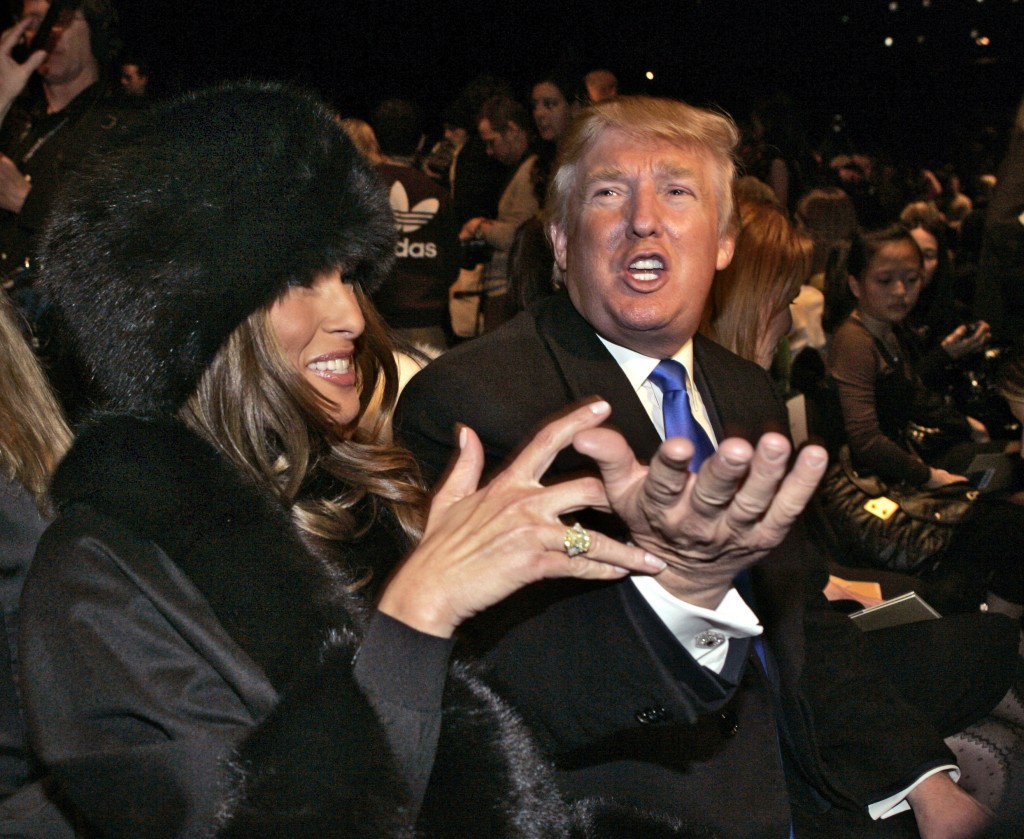 HOLD HOLD In this Feb. 7, 2007, file photo, Donald Trump and his wife, Melania, wearing a fur hat, talk to people on the runway as they sit in the fro