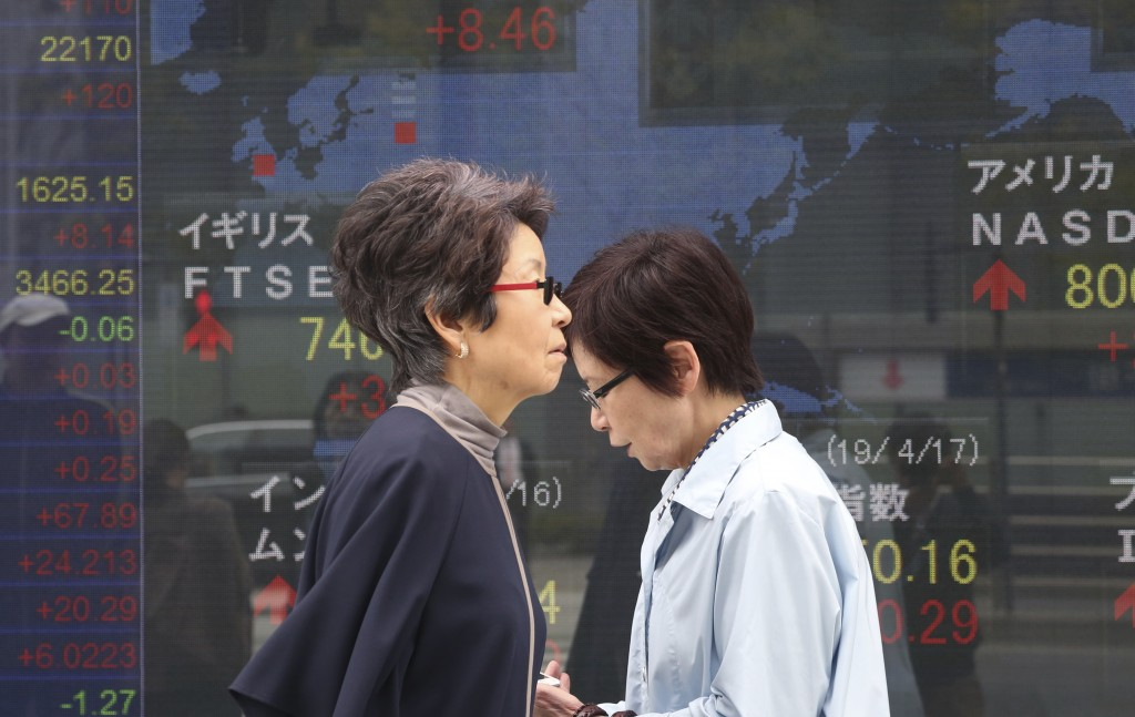 People walk by an electronic stock board of a securities firm in Tokyo, Wednesday, April 17, 2019. Shares were mixed in a narrow range Wednesday as Ch