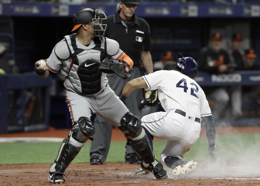 Baltimore Orioles catcher Jesus Sucre, left, looks to throw after Tampa Bay Rays' Tommy Pham scored on a sacrifice fly by Yandy Diaz during the fourth