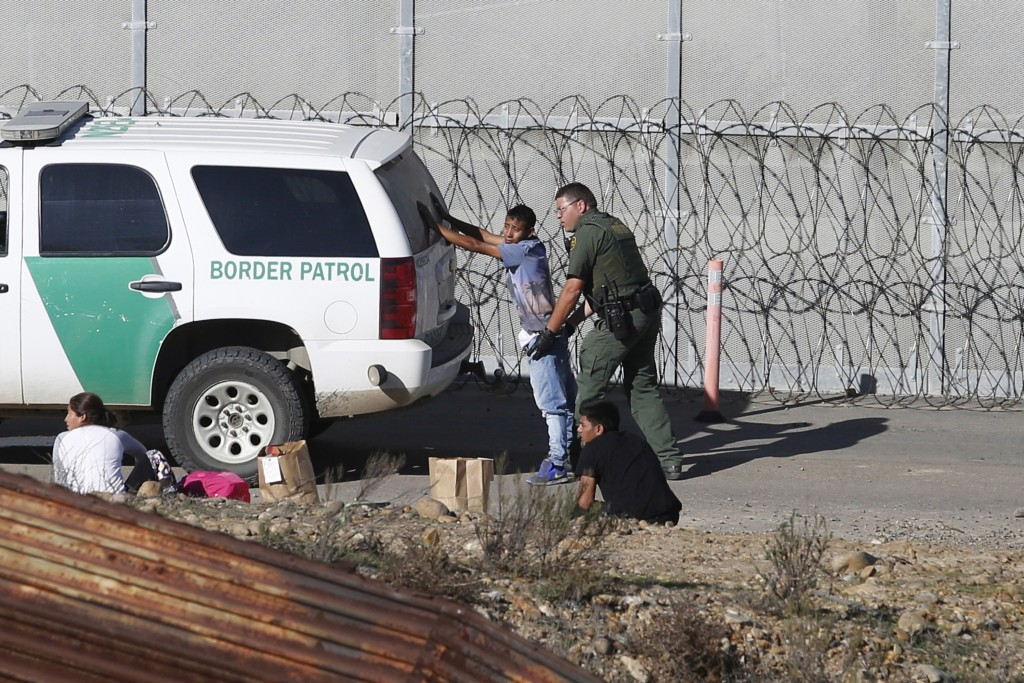 FILE - In this Dec. 15, 2018, file photo, Honduran asylum seekers are taken into custody by U.S. Border Patrol agents after the group crossed the U.S.