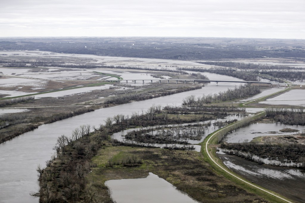 In this Friday, April 12, 2019 photo, the highway 34 bridge spans the Missouri River and it's flooded banks between La Platte, Nebraska and Glenwood,
