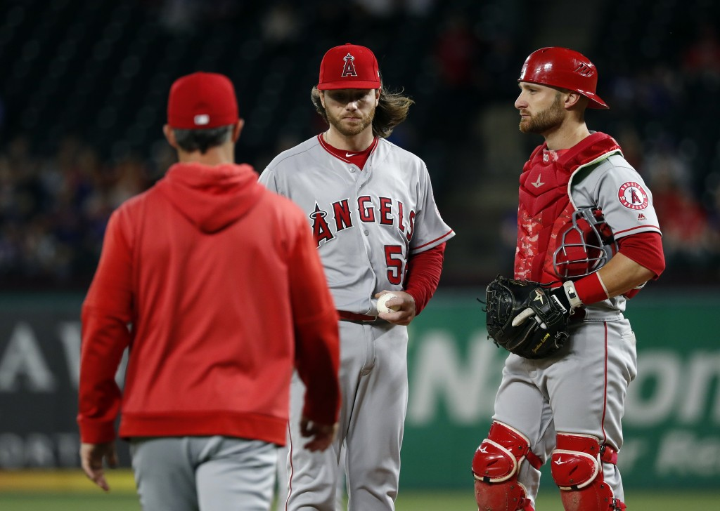 Los Angeles Angels manager Brad Ausmus, left, walks out to take the ball from relief pitcher Dillon Peters, center, as catcher Jonathan Lucroy stands