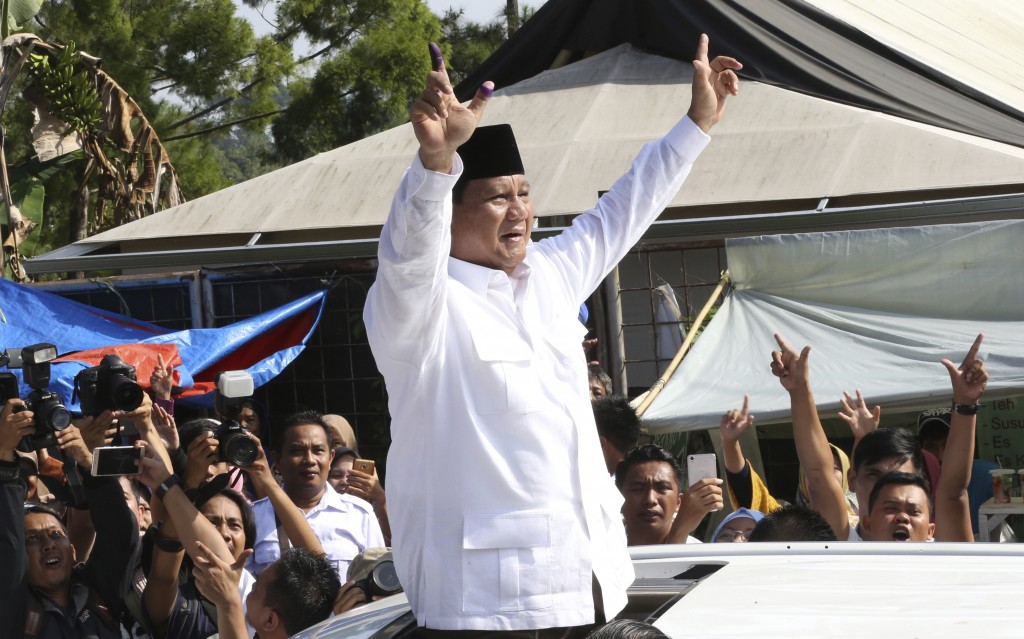 Indonesian presidential candidate Prabowo Subianto greets to his supporters after casting his vote at a polling station in Bogor, Indonesia, Wednesday...