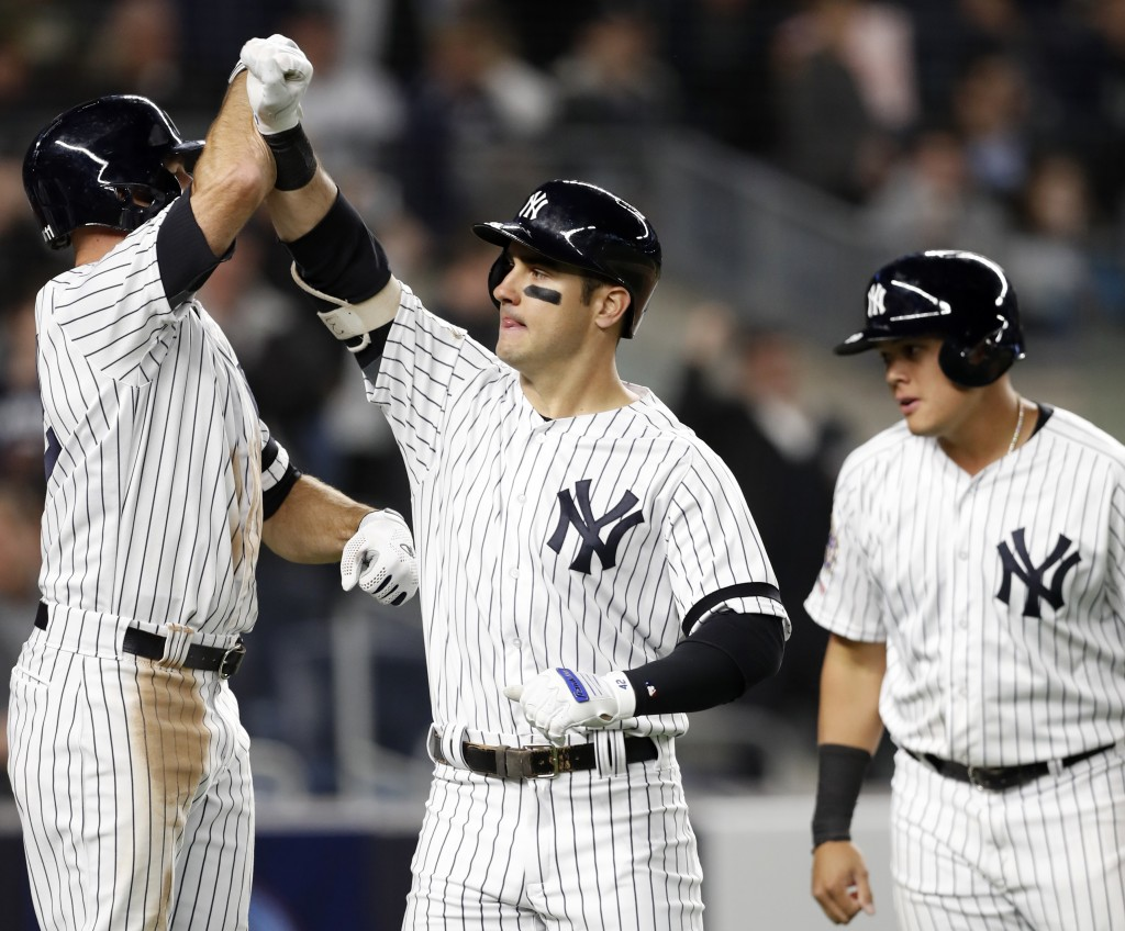 New York Yankees' Brett Gardner, left celebrates with the Mike Tauchman after Tauchman hit a sixth-inning, three-run home run off Boston Red Sox's Era