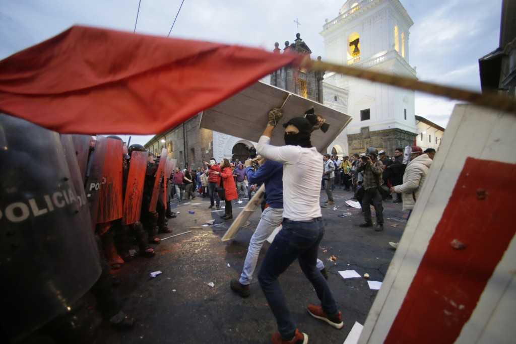 Protesters clash with police blocking them from advancing closer to the presidential palace in Quito, Ecuador, Tuesday, April 16, 2019. Protesters wer