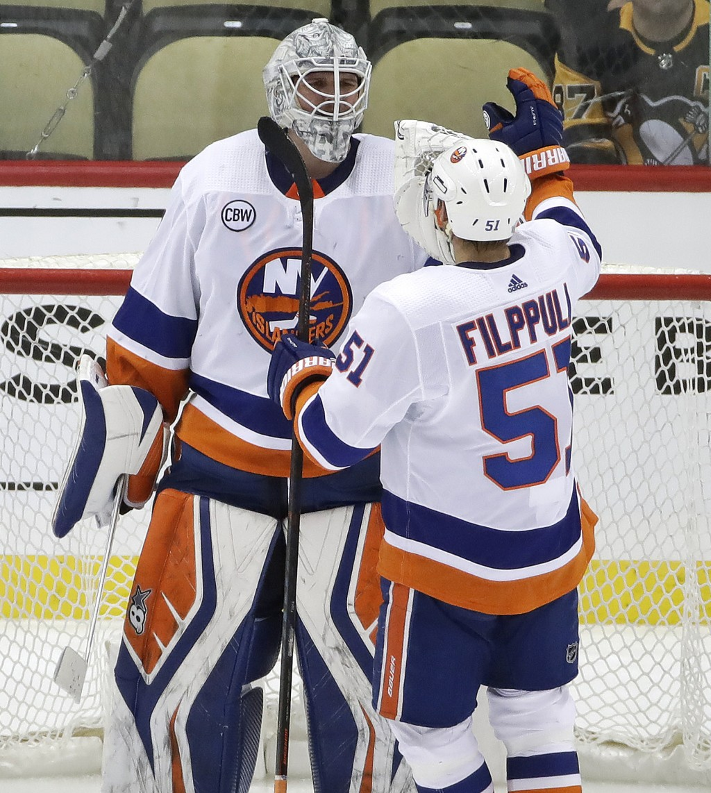 New York Islanders goaltender Robin Lehner (40) celebrates with Valtteri Filppula at the end of Game 4 of the team's NHL hockey first-round playoff se...