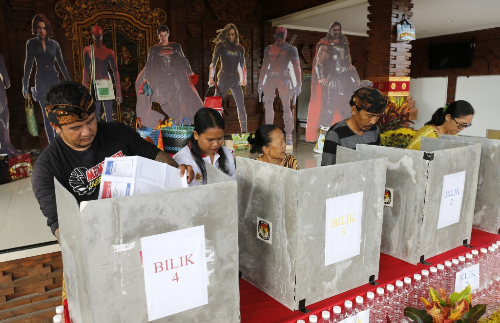 People cast their ballots in front of movie Avengers characters cutoutsvat a polling station during election in Bali, Indonesia on Wednesday, April 17