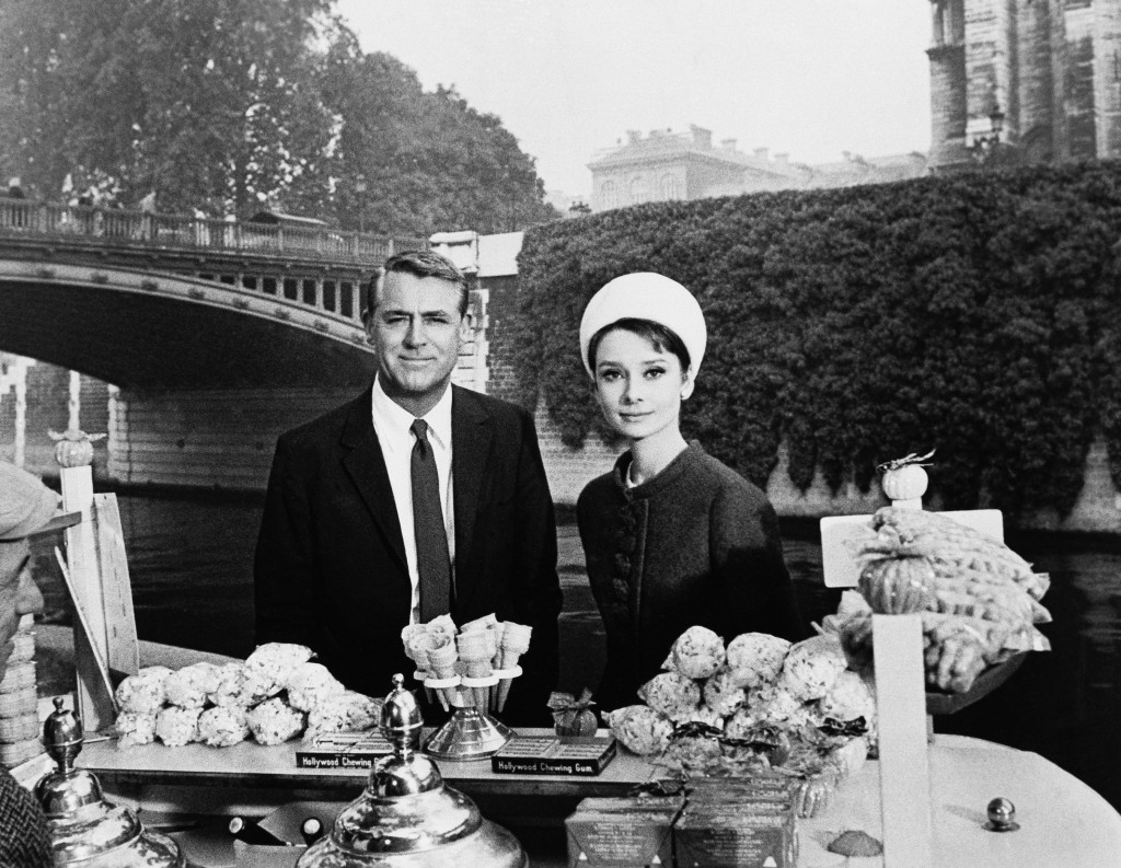 """FILE - In this October 1963 file photo, actors Cary Grant and Audrey Hepburn are photographed for the film """"Charade,"""" aboard a boat in the Seine River"""
