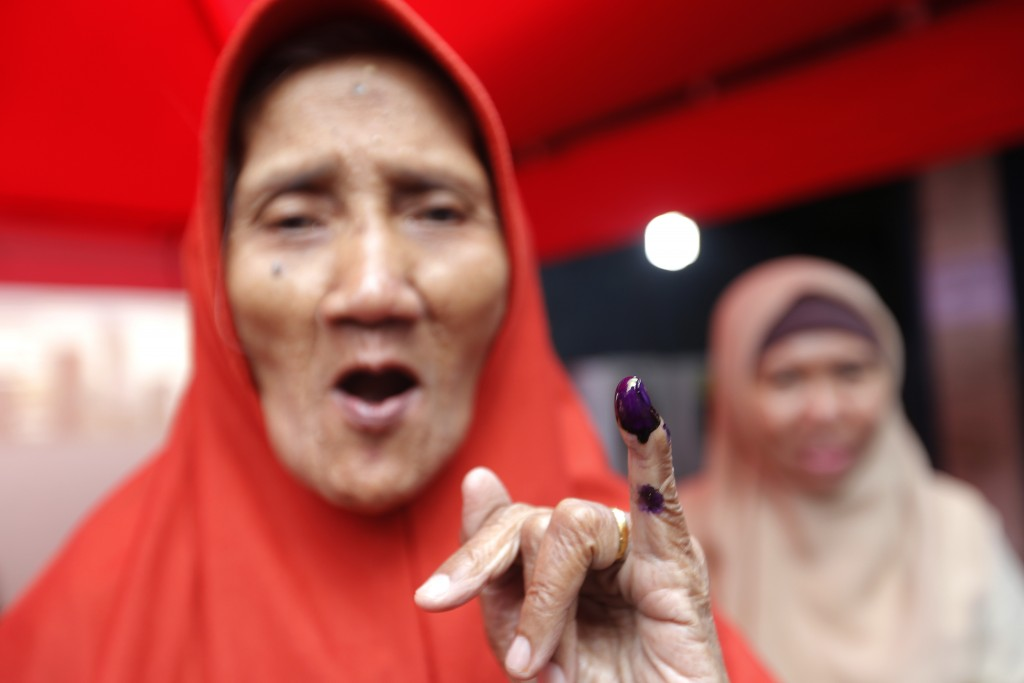 A woman shows her inked finger after casting her ballot at a polling station during the election in Jakarta, Indonesia, Wednesday, April 17, 2019. Vot...