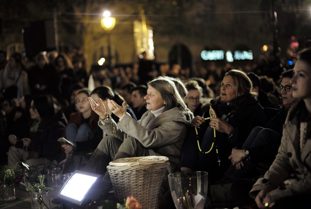 People attend a vigil in Paris, Tuesday April 16, 2019. Firefighters declared success Tuesday in a more than 12-hour battle to extinguish an inferno e