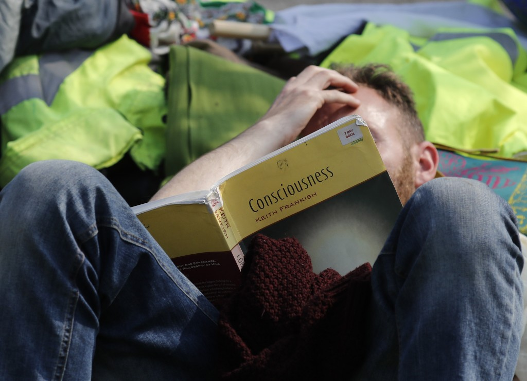 A protestor on Waterloo Bridge reads a book as the road is blocked in London, Wednesday, April 17, 2019. The group Extinction Rebellion is calling for