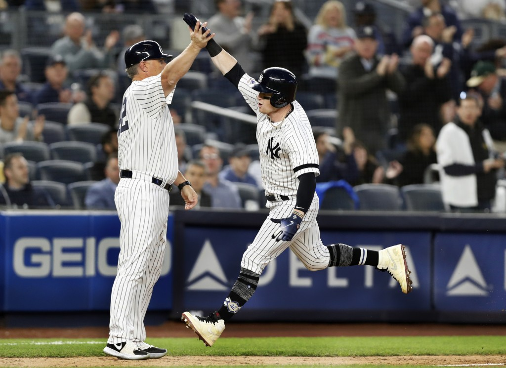 New York Yankees' Clint Frazier, right, trades high-fives with third base coach Phil Nevin after hitting a solo home run off Boston Red Sox starting p