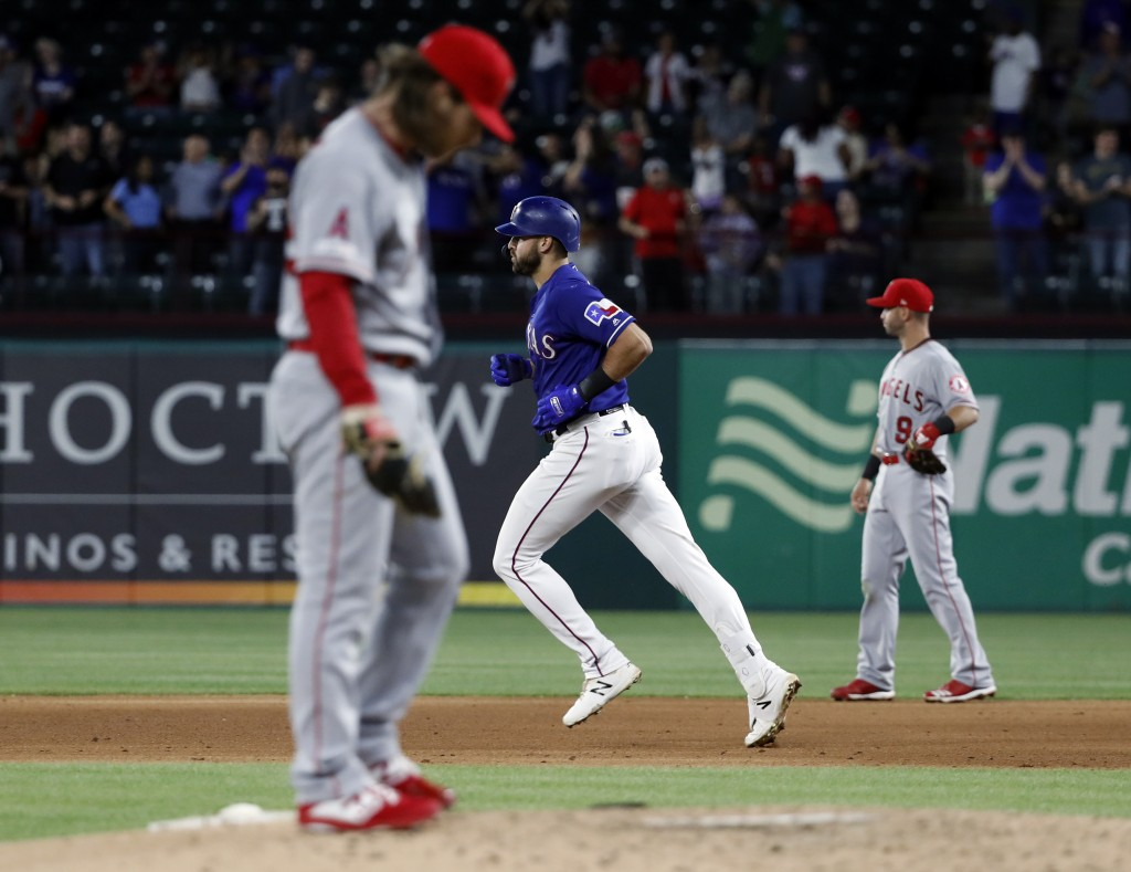 Los Angeles Angels relief pitcher Dillon Peters, left, stands on the mound and second baseman Tommy La Stella looks to the outfield as Texas Rangers'