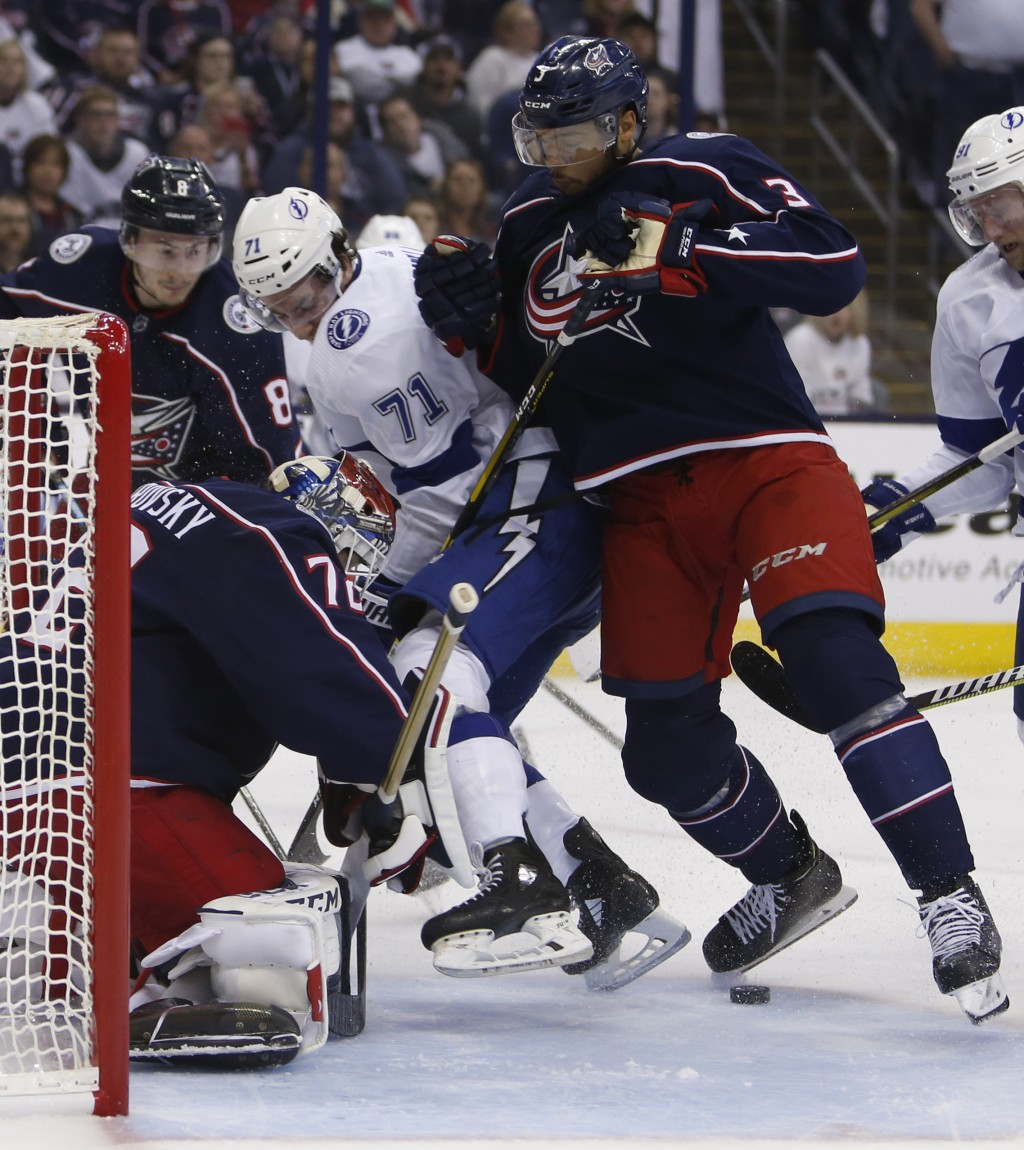 Columbus Blue Jackets' Sergei Bobrovsky, left, of Russia, makes a save as teammate Seth Jones, right, and Tampa Bay Lightning's Anthony Cirelli fight