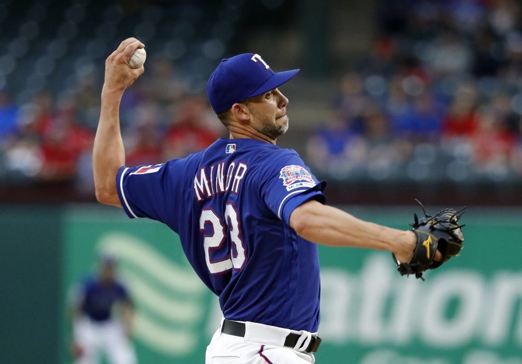 Texas Rangers starting pitcher Mike Minor throws to a Los Angeles Angels batter during the first inning of a baseball game in Arlington, Texas, Tuesda
