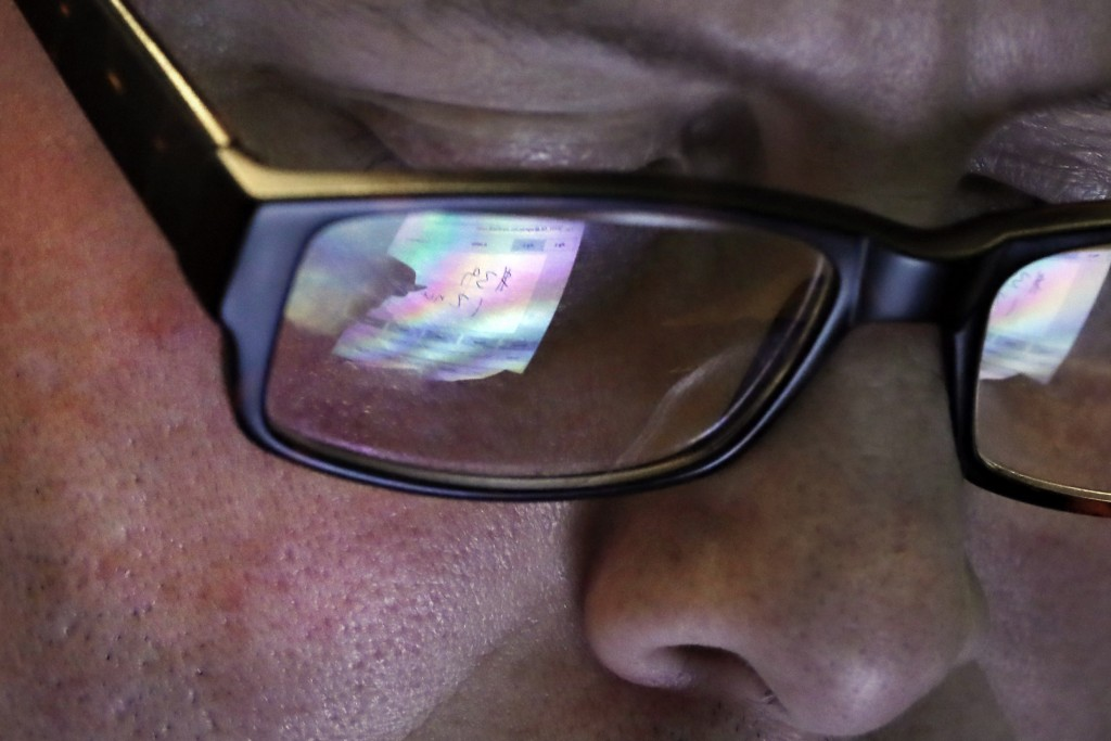 FILE- In this April 11, 2019, file photo trader Jeffrey Vazquez's glasses reflect the screen of his handheld device as he works on the floor of the Ne...