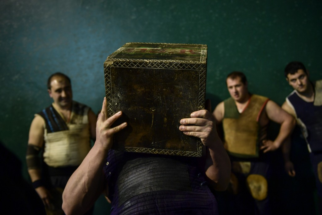 In this Saturday, April 6, 2019 photo, a basque stone lifter holds a 100 kilograms stone, during an exhibition in the basque village of Azkoitia, nort
