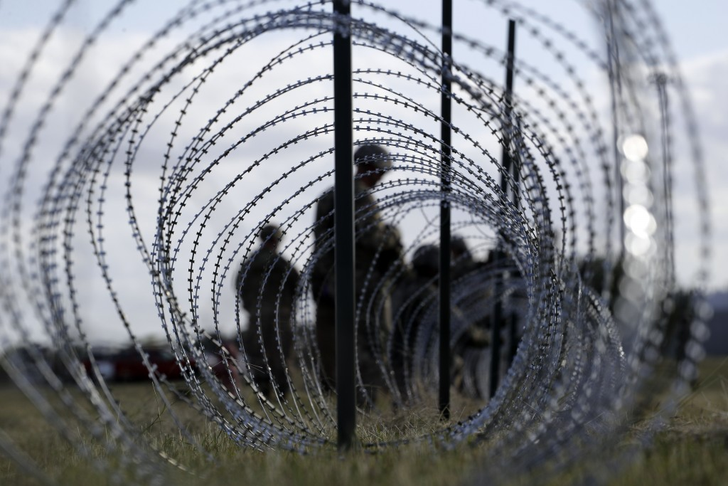 FILE--In this Nov. 3, 2018, file photo, members of the U.S. Army build a razor wire fence around area for tents near the U.S.-Mexico International bri