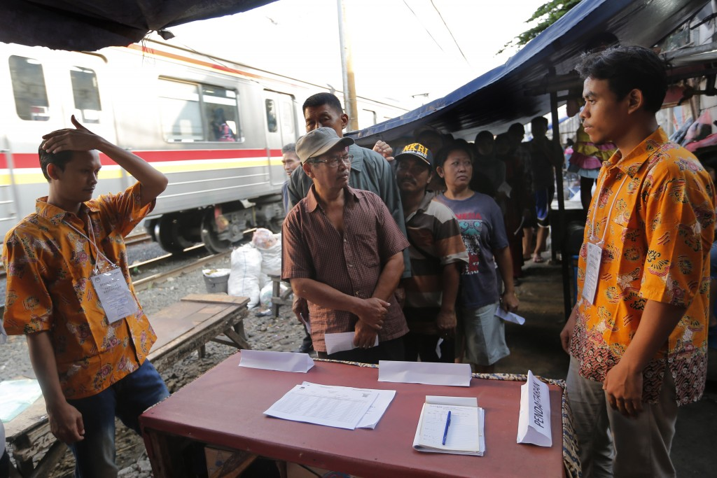 Indonesians queue up to cast their votes during the election near a railway track at a slum in Jakarta, Indonesia, Wednesday, April 17, 2019. Voting i...