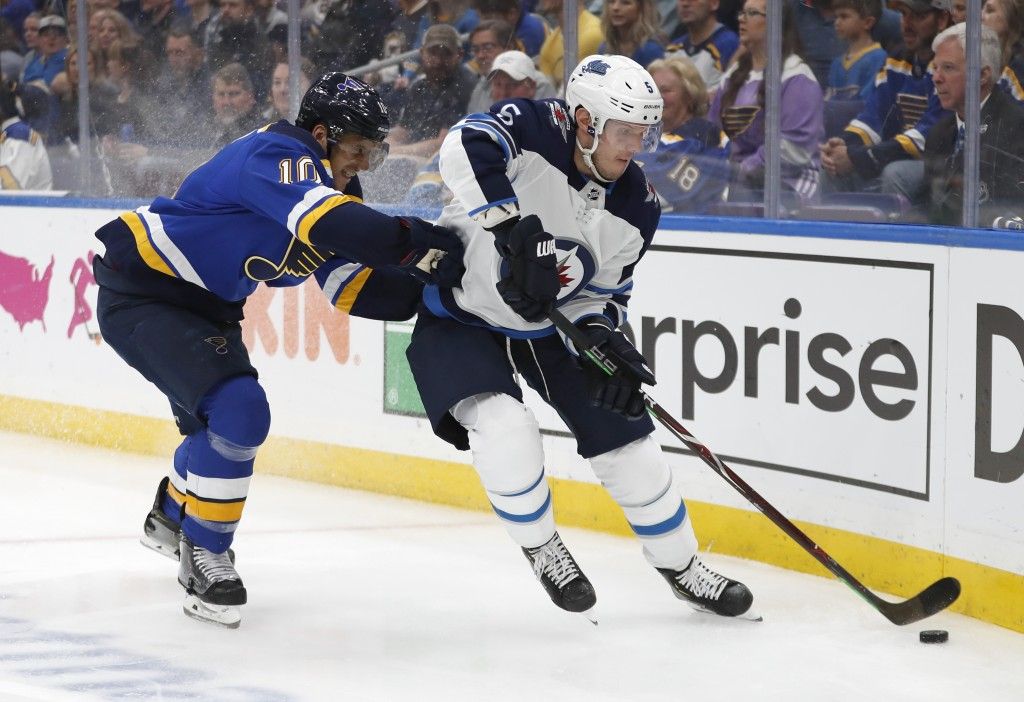 St. Louis Blues center Brayden Schenn (10) tries to slow down Winnipeg Jets defenseman Dmitry Kulikov (5), of Russia, during the second period in Game