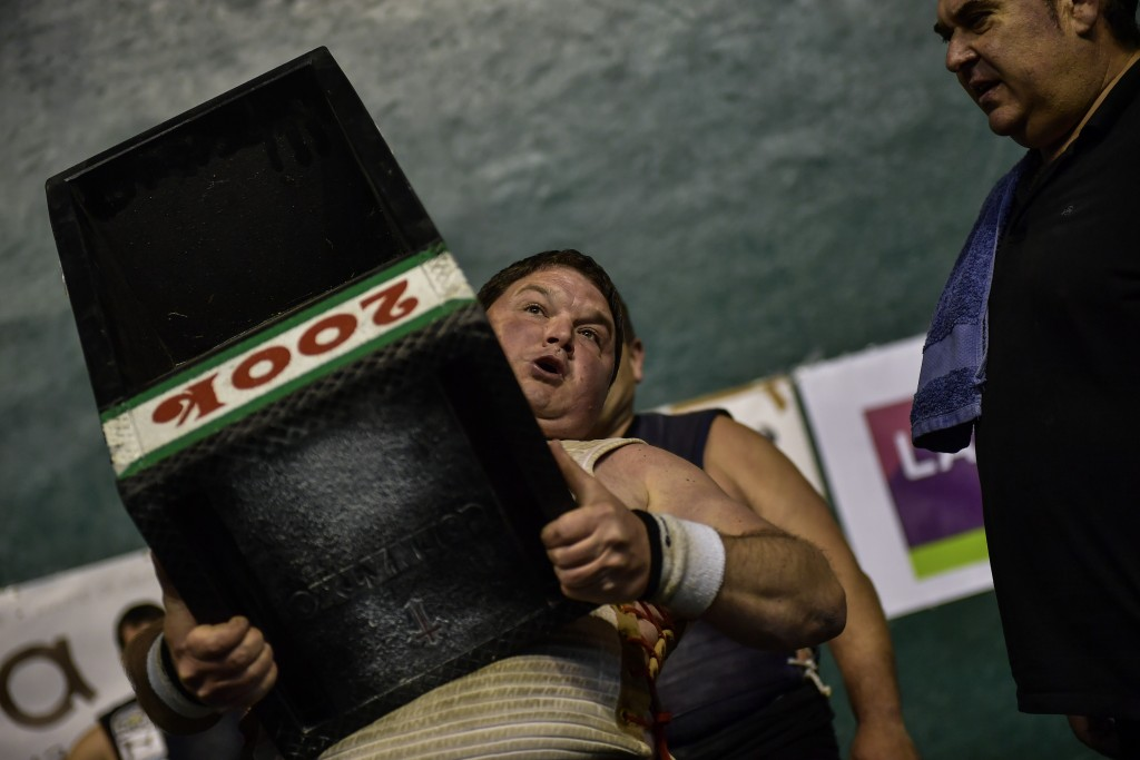 In this Saturday, April 6, 2019 photo, a basque stone lifter holds a 200 kilograms stone, during an exhibition in the basque village of Azkoitia, nort