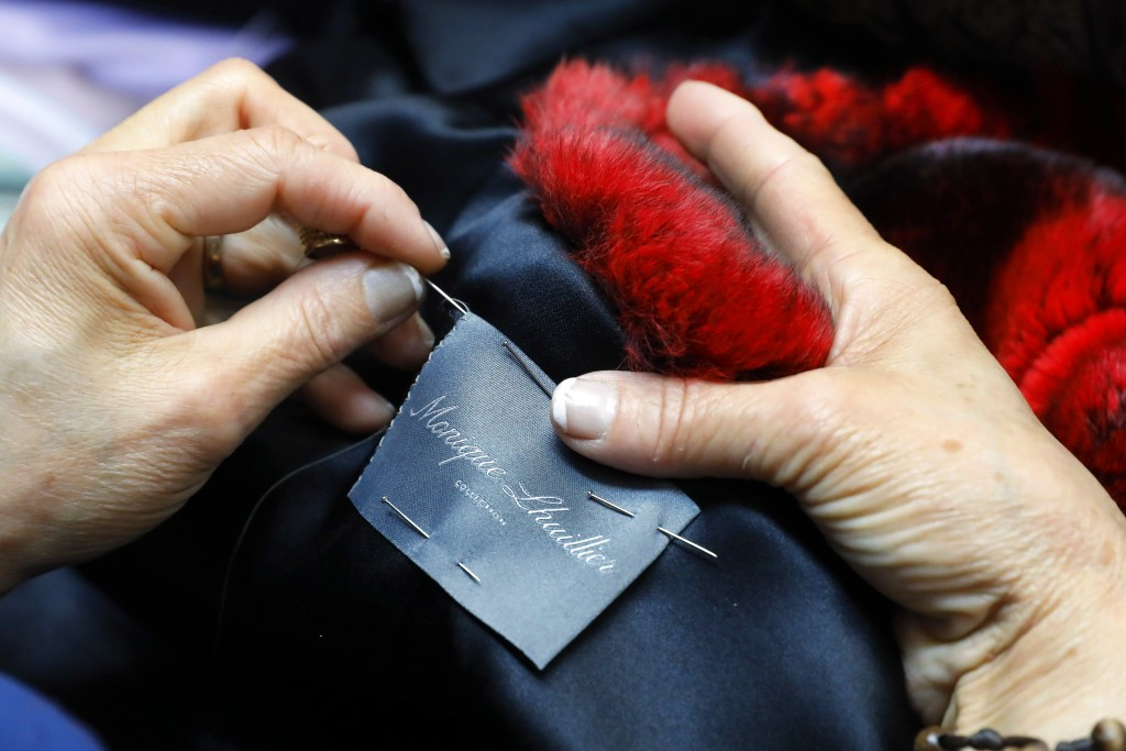 In this April 10, 2019, photo, seamstress Sonia Genao sews a Monique Lhuillier label in a coat at Pologeorgis Furs in New York. A burgeoning movement