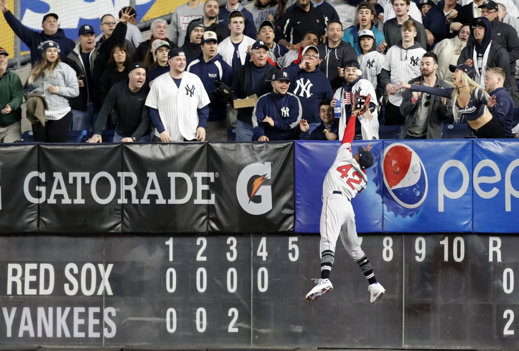 Boston Red Sox right fielder Mookie Betts leaps for but can't get to a solo home run by New York Yankees' Clint Frazier during the fourth inning of a ...