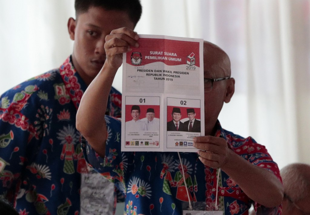 An electoral worker inspects a presidential ballot during the election at a polling station in Jakarta, Indonesia, Wednesday, April 17, 2019. Voting i...