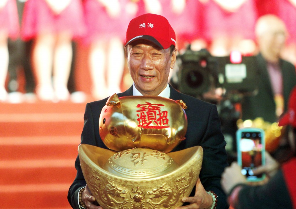 FILE - Terry Gou, chairman of Hon Hai Precision Industry Co. Ltd., also known as Foxconn, holds New Year's lucky charm during the company's annual car