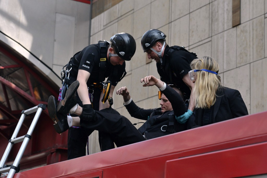 Police begin to remove climate activists who glued themselves on top of a Dockland Light Railway train at Canary Wharf station in east London as part