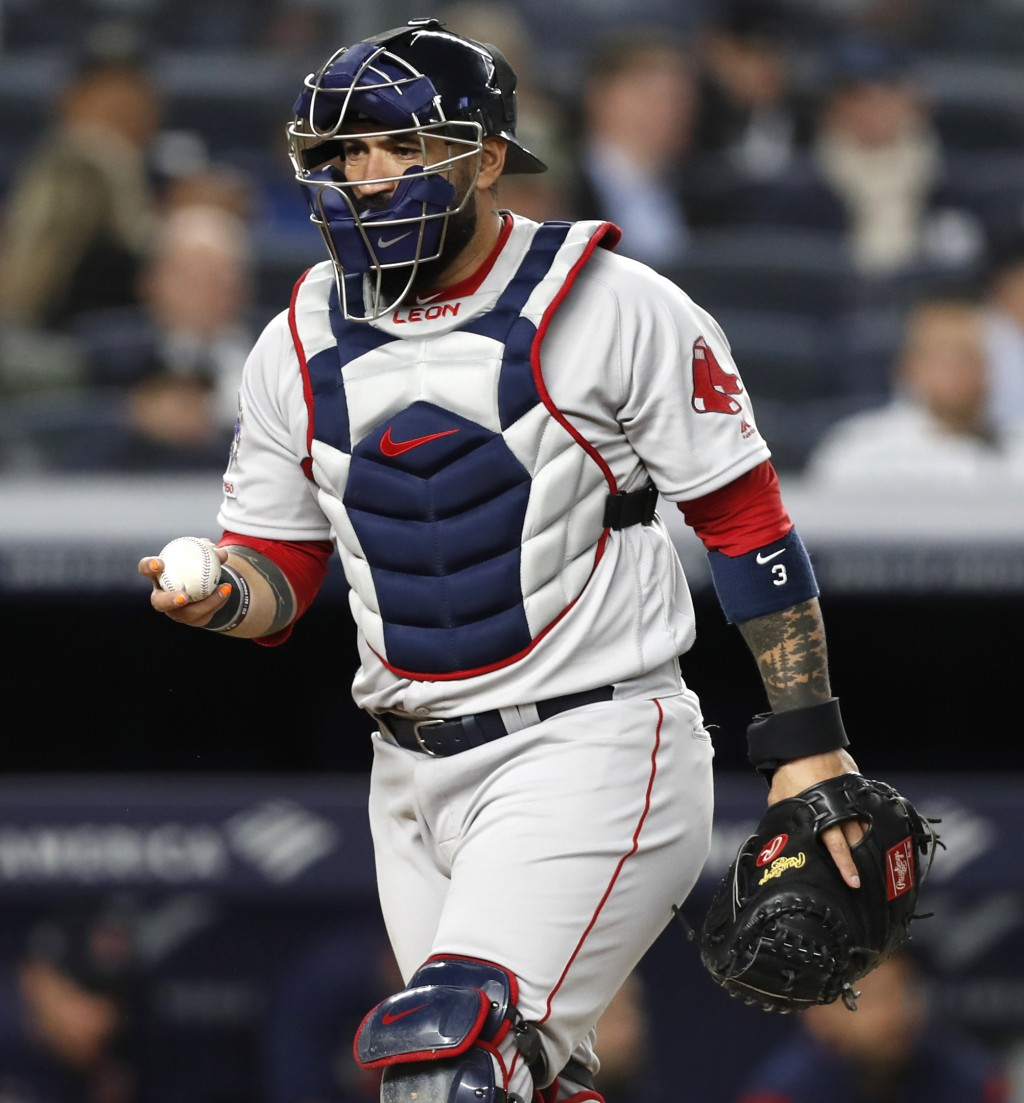 Boston Red Sox catcher Sandy Leon returns to his position after picking up a foul ball during the sixth inning of the team's baseball game against the