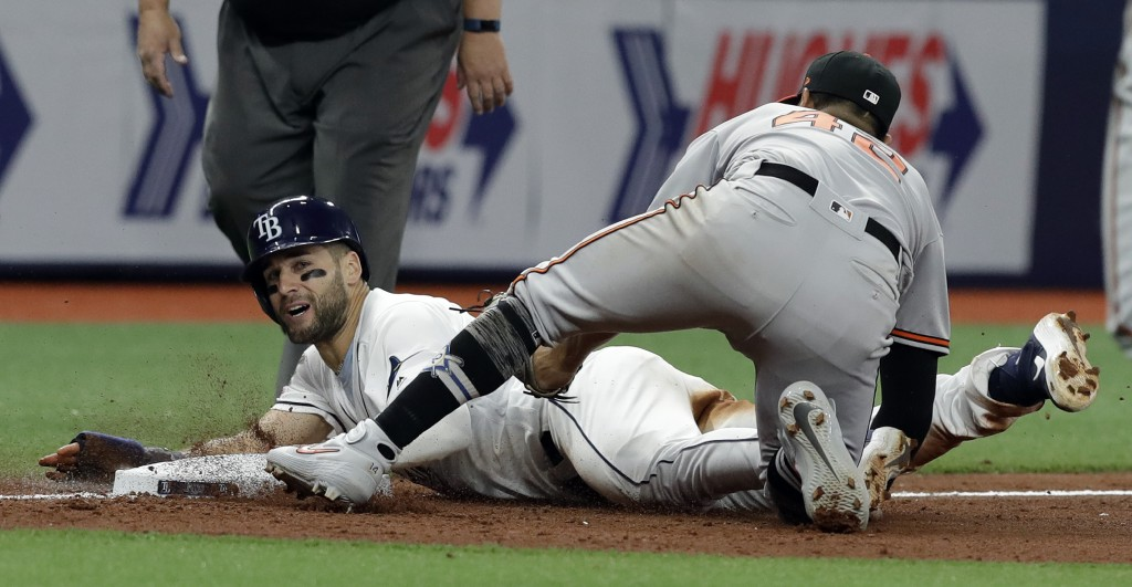 Tampa Bay Rays' Kevin Kiermaier, left, is tagged out by Baltimore Orioles' Rio Ruiz while trying to steal third base during the seventh inning of a ba