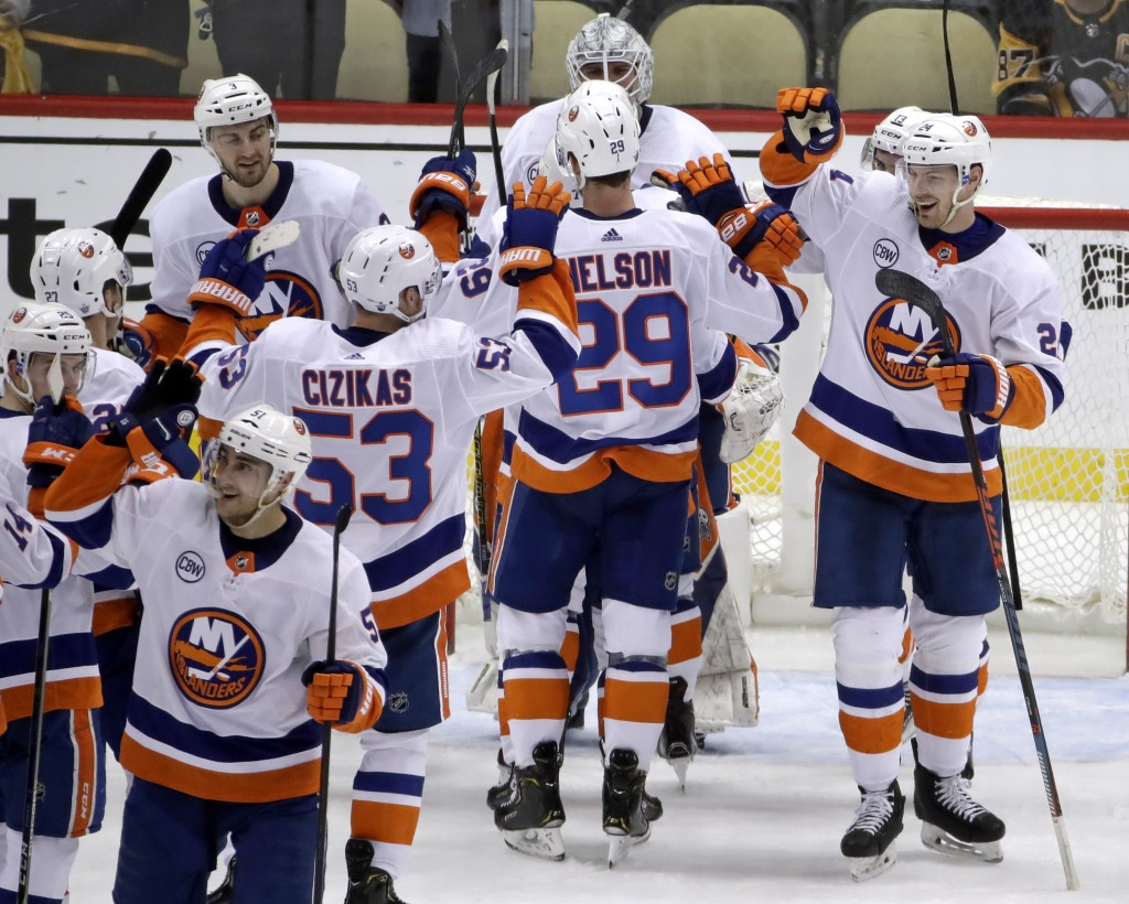 New York Islanders celebrate at the end of Game 4 of an NHL hockey first-round playoff series against the Pittsburgh Penguins in Pittsburgh, Tuesday, ...