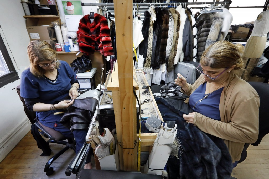 In this April 10, 2019, photo, seamstresses Sonia Genao, left, and Juana Rodrize work on coats at Pologeorgis Furs in New York. At the height of the f
