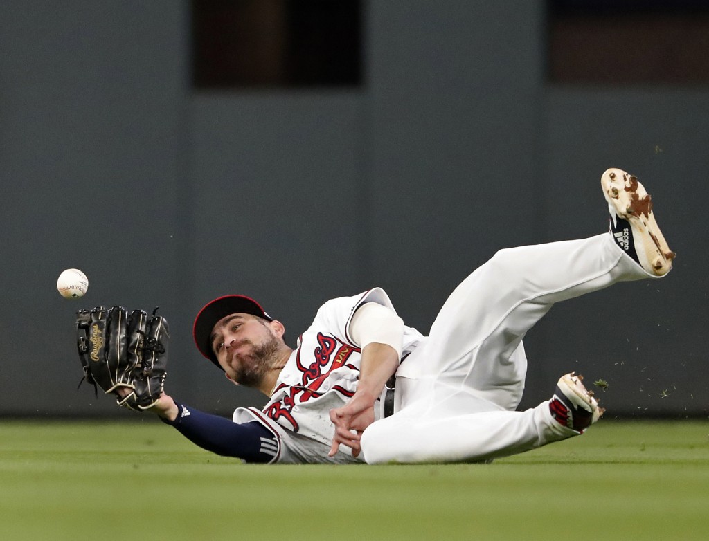 A ball hit for an RBI-single by Arizona Diamondbacks' Nick Ahmed gets away from Atlanta Braves center fielder Ender Inciarte (11) in the fourth inning...