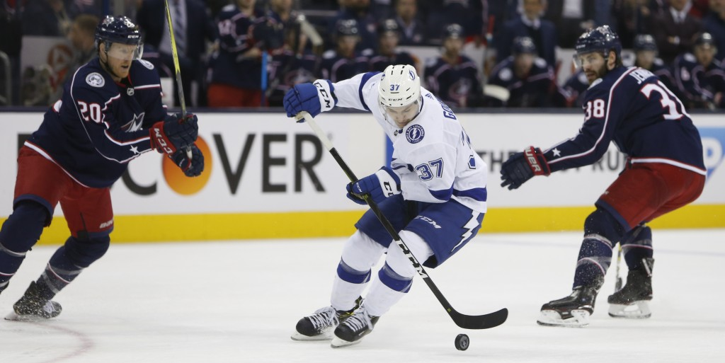 Tampa Bay Lightning's Yanni Gourde, center, carries the puck between Columbus Blue Jackets' Riley Nash, left, and Boone Jenner during the second perio
