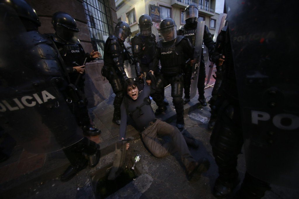 A man is detained by police blocking protesters from advancing closer to the presidential palace in Quito, Ecuador, Tuesday, April 16, 2019. Protester