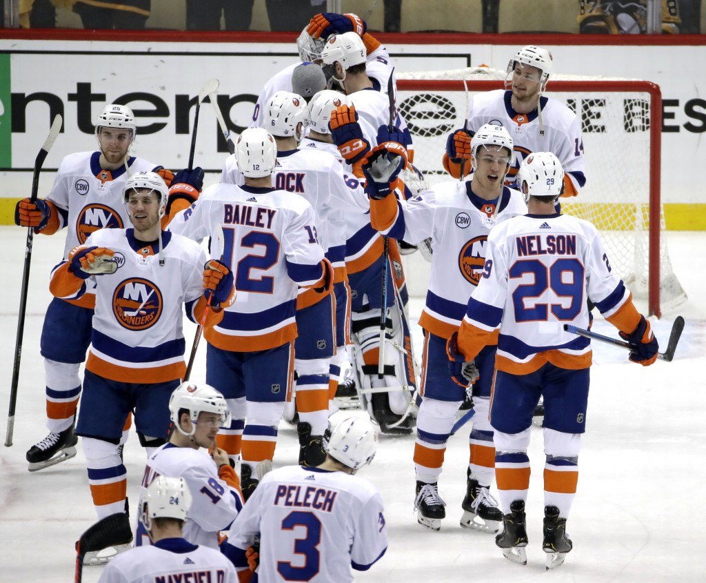 The New York Islanders celebrate at the end of Game 4 of an NHL hockey first-round playoff series against the Pittsburgh Penguins in Pittsburgh, Tuesd