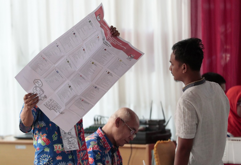 An electoral worker shows a legislative ballot to a voter during the election at a polling station in Jakarta, Indonesia, Wednesday, April 17, 2019. V...
