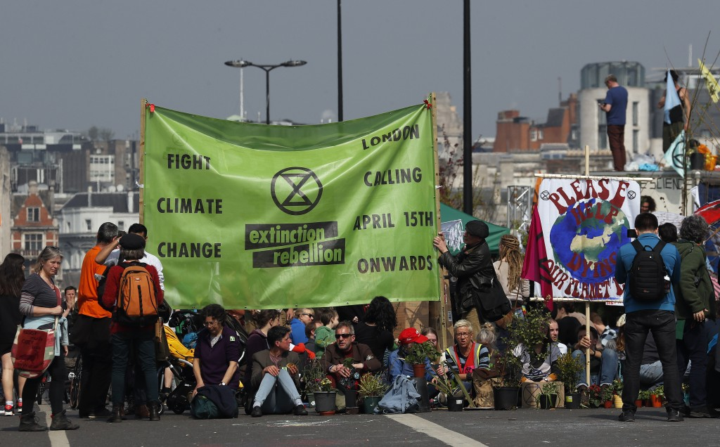 Protestors sit on the road of the blocked Waterloo Bridge in London, Wednesday, April 17, 2019. The group Extinction Rebellion is calling for a week o