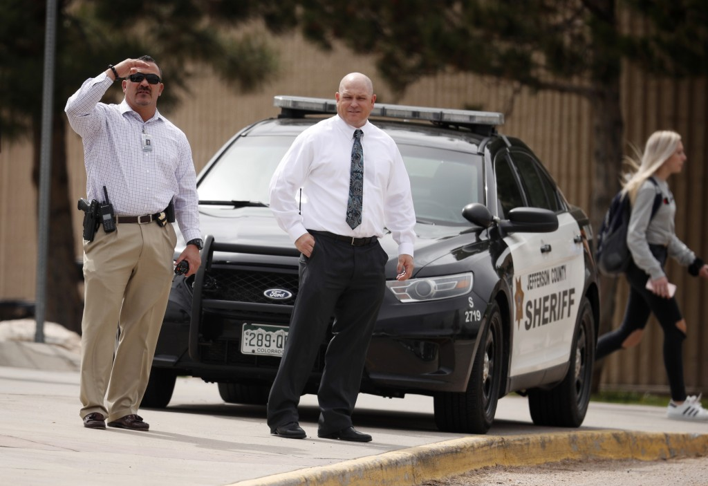 Columbine High School principal Scott Christy, right, joins an officer in watching as students leave the school late Tuesday, April 16, 2019, in Littl