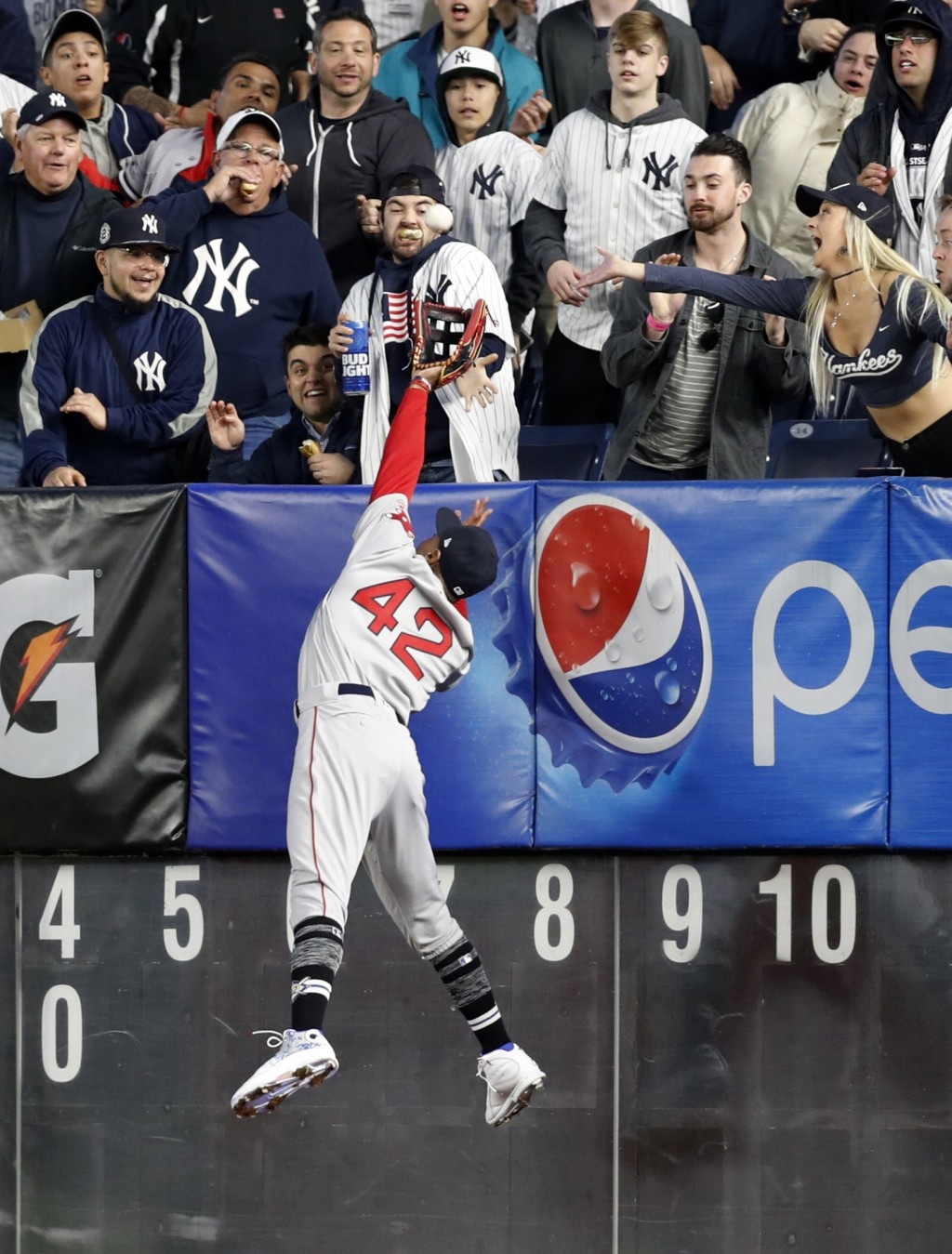Boston Red Sox right fielder Mookie Betts leaps for but can't get to a solo home run by New York Yankees' Clint Frazier during the fourth inning of a