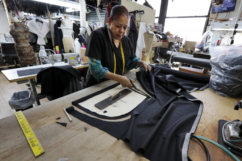 In this April 10, 2019, photo, Maria Rodriguez uses a pattern as she cuts lining for a coat at Pologeorgis Furs in New York. The fur trade is consider