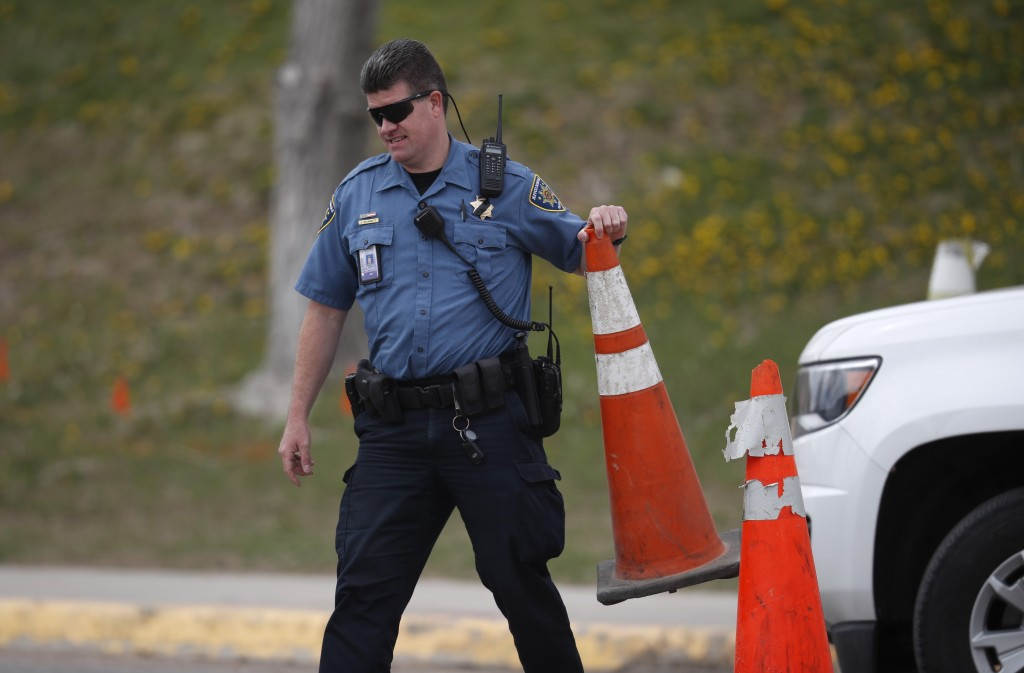 A Jefferson County, Colo. Schools officer blocks a driveway with a pylon outside Columbine High School as students leave late Tuesday, April 16, 2019,