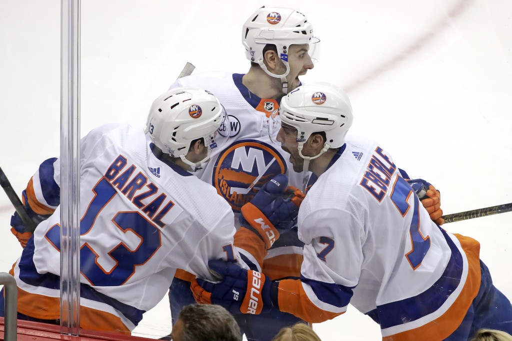 New York Islanders' Jordan Eberle (7) celebrates with Adam Pelech, center, and Mathew Barzal (13) after scoring against the Pittsburg Penguins during