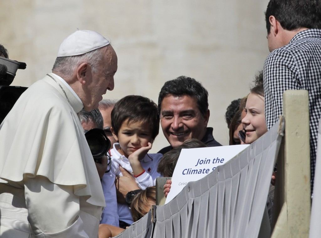 Pope Francis greets Swedish teenage environmental activist Greta Thunberg, right, during his weekly general audience in St. Peter's Square, at the Vat