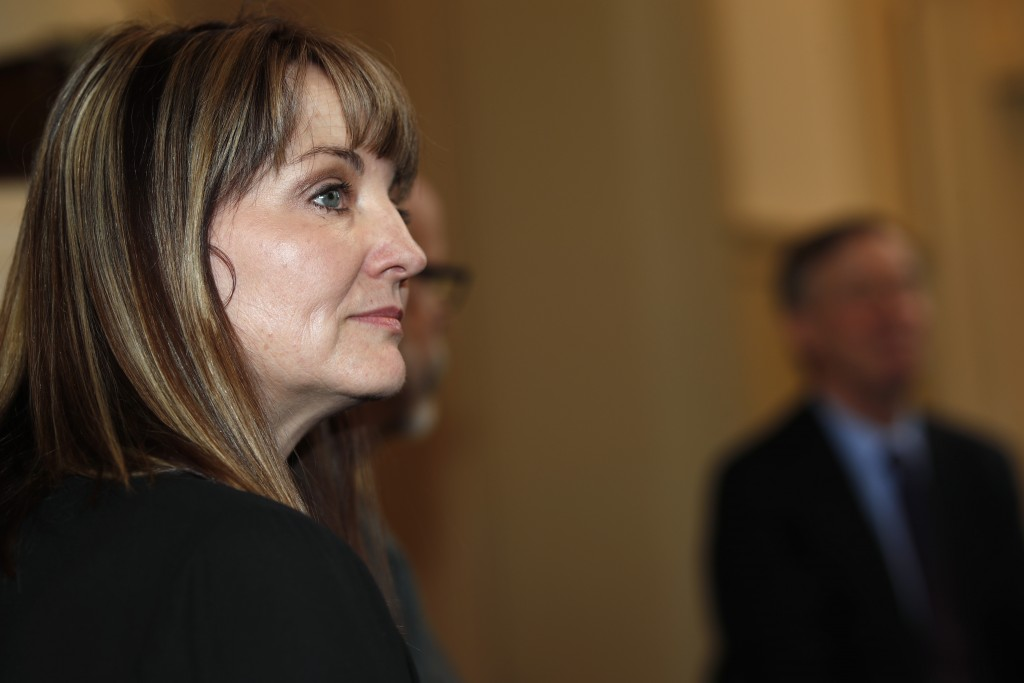 Coni Sanders, front, who lost her father, Dave, in the massacre at Columbine High School, listens as Democratic presidential hopeful John Hickenlooper