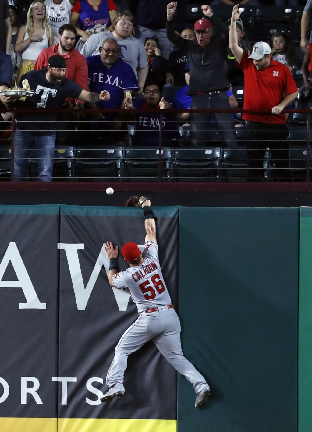 Fans watch as a ball that bounced off the top of Los Angeles Angels right fielder Kole Calhoun's glove falls over the wall for a two-run home run by T
